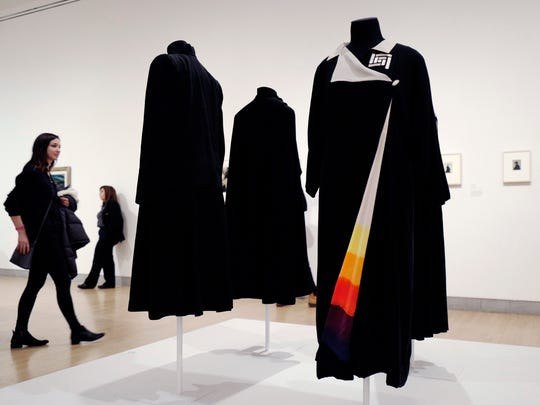 """In this March 16, 2017 photo, a woman walks by a kimono-style coat, right, worn by artist Georgia O'Keeffe, now on exhibit at the Brooklyn Museum in New York. The show """"Georgia O'Keeffe: Living Modern"""" highlights her role as a style icon."""