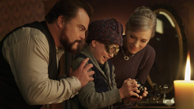 "Uncle Jonathan (Jack Black, left) and Mrs. Zimmerman (Cate Blanchett, right) wait to see if Jonathan's nephew Lewis (Owen Vaccaro) can solve a mystery with a Magic 8 ball in ""The House With a Clock in Its Walls."""