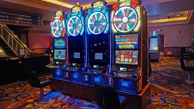 The middle two slot machines in this row at Twin River Casino in Lincoln are not playable to maintain the social distance of six feet between players.