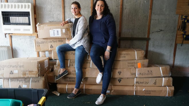 Christine Clarke, left, and Jennifer Oser, treasurer and president of the Walter E. Ranger Elementary School PTO, respectively, sit on the pile of boxes that contain the tents that they cannot use.