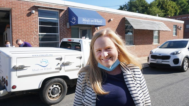Meghan Grady, executive director of Meals on Wheels of Rhode Island, stands outside the agency's Providence office as delivery vehicles are loaded earlier this month.