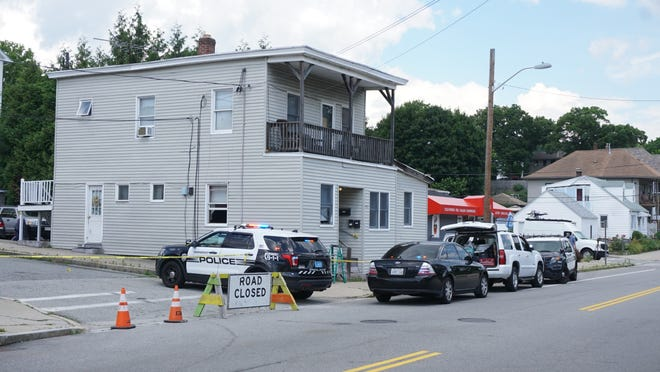 Police cars outside 408 Cass Ave. in Woonsocket on Friday.