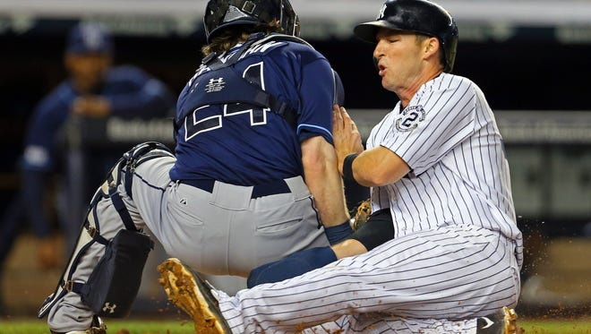 Yankees second baseman Stephen Drew slides into home and is tagged out by Tampa Bay Rays catcher Ryan Hanigan during the fifth inning Tuesday at Yankee Stadium.