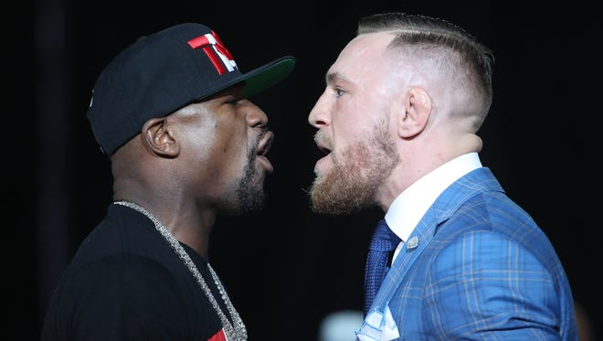 Floyd Mayweather, left, and Conor McGregor jaw at each other during a world tour press conference to promote their fight.