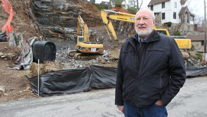 Cliff Schneider stands in front of rock crushing that was taking place this month at a property along Avondale Road in Yonkers.