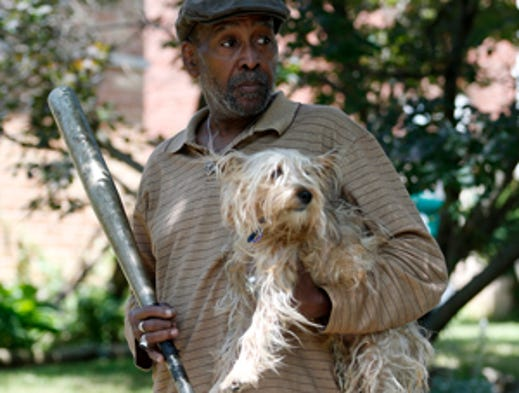 Leslie McElratch Jr. holds the bat that his daughter used to fight two pit bulls off of his granddaughter, 6-year-old Zainabou Drame.