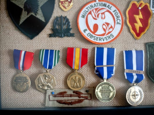 Medals of Staff Sgt. Scott Lawson hang on the wall in Mary and Wayne Lawson's St. Clair home. Staff Sgt. Scott Lawson is being posthumously awarded the Michigan National Guard Distinguished Service Medal for his heroism during the Battle of Fallujah.