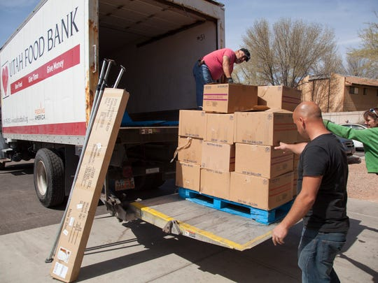 Volunteers unload donations from area grocery stores from a Utah Food Bank truck.
