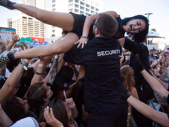Crowd surfers pass over the front rail during a performance