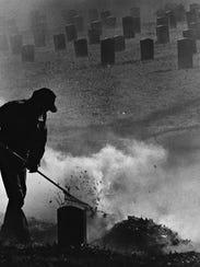 Asheville city employee Ed Ray uses a rake to keep