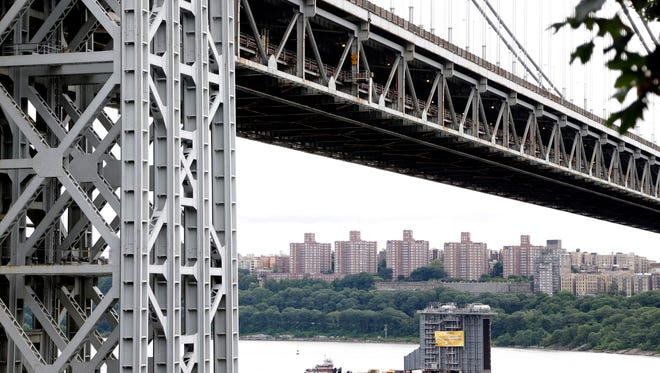 A large generator passes under the George Washington Bridge as seen from Fort Lee, N.J., Tuesday, Aug. 8, 2017. The 130-foot-(40-meter)-tall steam generator built along the Hudson River outside Albany is on a barge heading south for a New Jersey power plant.