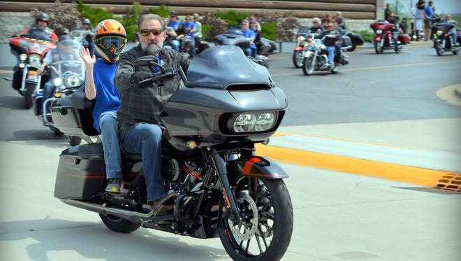 "Bryce Kane of Oconto, a cancer survivor for more than five years, rides with Rick Vandervest as the 15th annual Jerry Parins ""Cruise for Cancer"" departs from Vandervest Harley-Davidson on June 9."