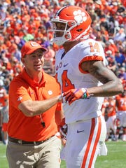 Clemson head coach Dabo Swinney, left, congratulates Clemson wide receiver Diondre Overton (14) after he caught a touchdown pass during Clemson's NCAA college football spring game at Memorial Stadium in Clemson, S.C. on Saturday, April 8, 2017.