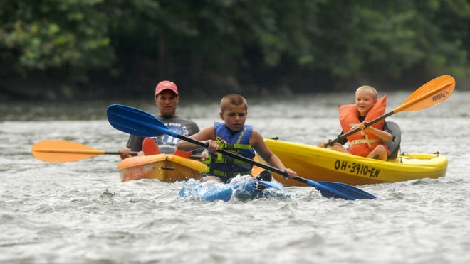 Cody Matthews kayaks with his family down the Black River Sunday morning.