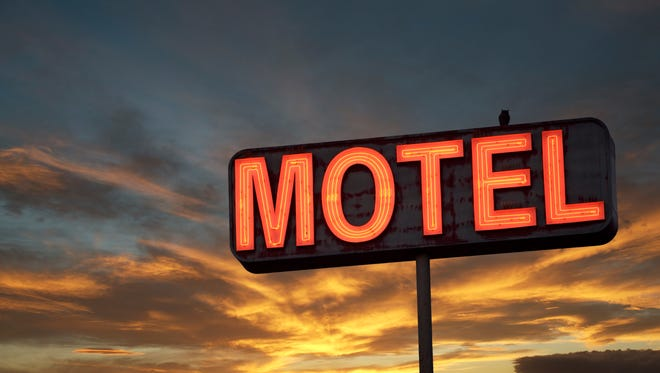 Motel sign with sunset