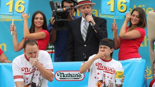 In this July 4, 2015 file photo, Joey Chestnut, left, and Matt Stonie compete in Nathan's Famous Fourth of July International Hot Dog Eating Contest men's competition Saturday in the Coney Island section in the Brooklyn borough of New York.