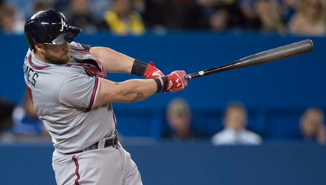 Atlanta Braves' Jonny Gomes hits a three-run double during first-inning baseball game action against the Toronto Blue Jays in Toronto on Sunday.