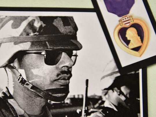 John Norman, one of the veterans being honored by Grove Library this month on its Military Honor Wall and History Wall, is shown with an image of the Purple Heart.