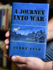 "Gerry Feld holds a copy of his novel, ""A Journey Into"