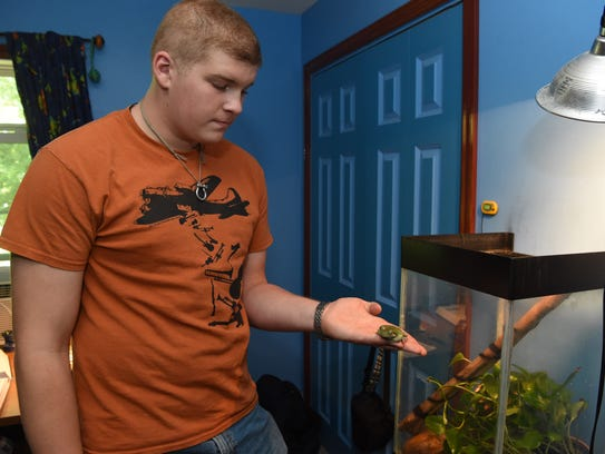 Jacob Jurain, 16, holds his pet frog Edsel in his New