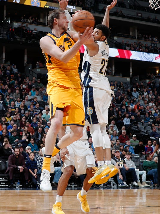 Utah Jazz forward Joe Ingles, front, of Australia, looks to pass the ball as he drives by Denver Nuggets guard Jamal Murray in the second half of an NBA basketball game Tuesday, Dec. 26, 2017, in Denver. The Nuggets won 107-83. (AP Photo/David Zalubowski)