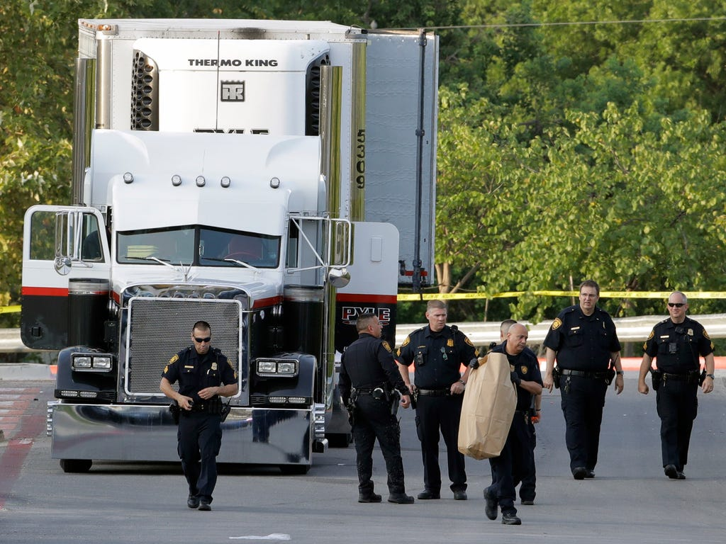 San Antonio police officers investigate the scene where eight people were found dead in a tractor-trailer loaded with at least 30 others outside a Walmart store in stifling summer heat in what police are calling a horrific human trafficking case in S