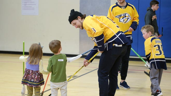 Nashville Predators players Filip Forsberg and Colton Sissons show children how to play hockey during a Brentwood YMCA Full Circle event Tuesday, March 14, 2017.