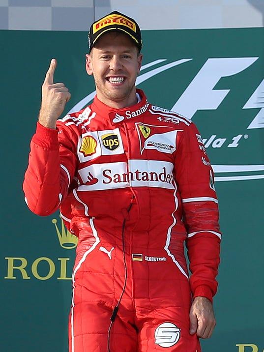 Ferrari driver Sebastian Vettel of Germany raises a finger after winning the Australian Formula One Grand Prix in Melbourne, Australia, Sunday, March 26, 2017. (AP Photo/Rick Rycroft)
