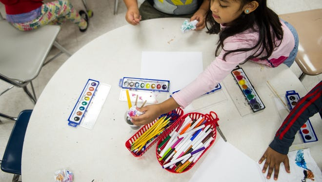 Angie Zelaya, 6, reaches for a paintbrush as she works on a painting during the Read to be Ready summer camp held at J.E. Moss Elementary School in Antioch, Tenn., Monday, July 3, 2017. The camps are a direct result of the state's literacy initiative, a multi-million dollar program to boost reading scores in the state and to help prevent summer reading loss among the state's highest need students. The camps are just one of the many pieces of the state's initiative.