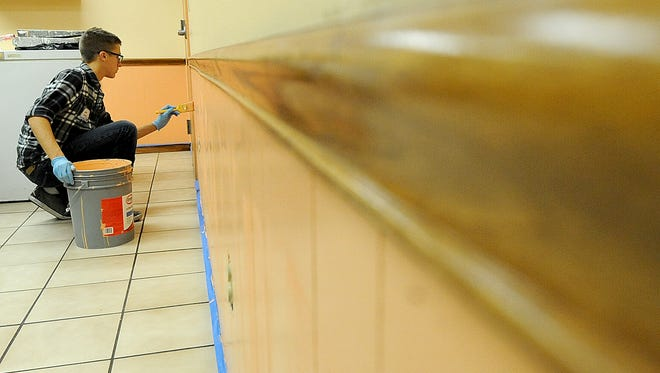 Josh Young, a 10th grader at Clear Fork, gives the dining room walls a Harmony House a fresh coat of paint on Tuesday.