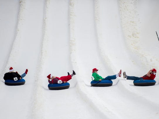 Santas race down the snow tubing park at Ober Gatlinburg