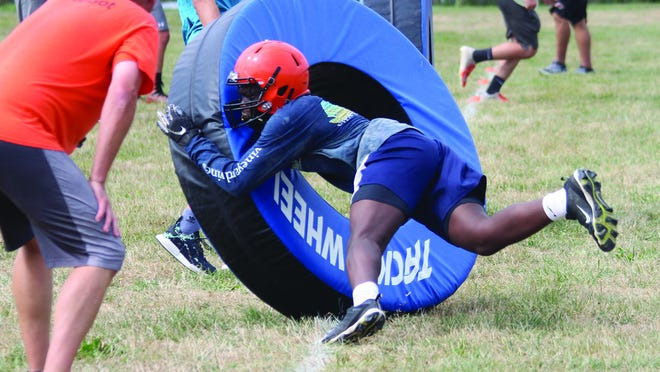 The Macomb football team goes through drills during the first day of practice last summer.