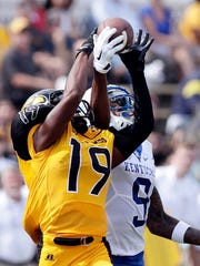 Southern Miss defensive back Curtis Mikell (19) breaks up a pass intended for Kentucky wide receiver Garrett Johnson (9) during the first half of an NCAA college football game in Hattiesburg.