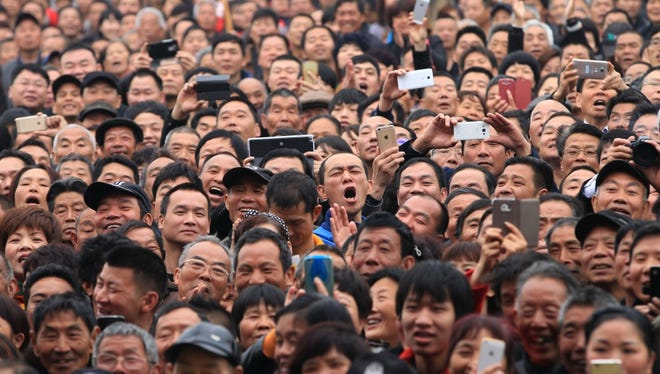 Spectators react as they watch a performance during a local martial arts cultural festival in Zhejiang province, China.
