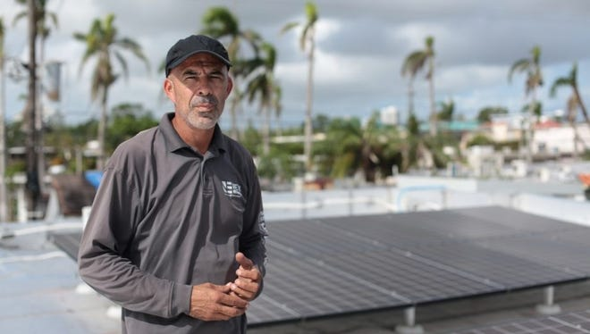 Technician Alexis Portalatin stands next to rooftop solar panels he is connecting to a new Tesla battery storage system in the San Juan suburb of Guaynabo.