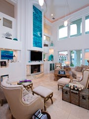 The first floor two story high living space takes in water views from floor to ceiling windows.  A sculpted fireplace wall with built ins and a beautiful blue art piece completes the picture