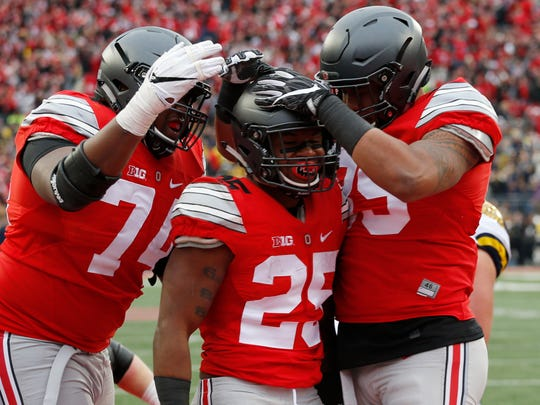 Ohio State running back Mike Weber, center, celebrates his touchdown against Michigan with teammates Jamarco Jones, left, and Luke Farrell during the second half of an NCAA college football game Saturday, Nov. 26, 2016, in Columbus, Ohio. Ohio State beat Michigan 30-27 in double overtime. (AP Photo/Jay LaPrete)