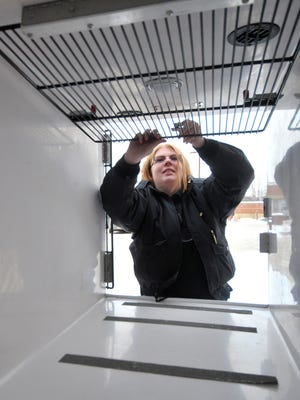 Humane officer Ashlee Bishop, 26, of Wausau, demonstrates how the kennel works in her truck Friday afternoon, Jan. 16, 2015, at the Wausau Police Department.