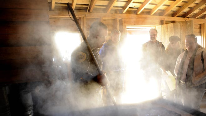 Former Highland County Sheriff Timothy Duff, left, explains the syrup-making process in his Highland County sugar house in 2012.