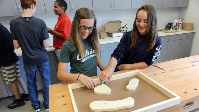 """From left, Kylee Adams, 11, of Philo, and Ali Carpenter, 11, of Chandlersville, test out their bristlebots during """"The Nuts, Bolts and Thingamajigs Summer Manufacturing Institute"""" five-day camp at Zane State College. Students, ages 11 to 14, learned about manufacturing careers and created marshmallow guns, lamps from PVC pipe, lava lamps and bristlebots, which are battery-powered motorized vibrating bristle heads powered."""