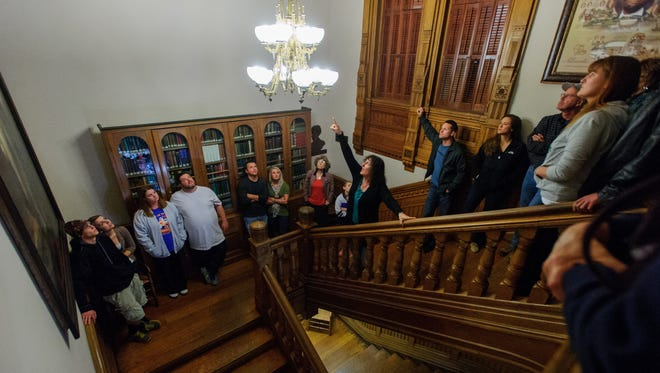 DANIEL R. PATMORE / SPECIAL TO EVANSVILLE COURIER & PRESS  Willard Library Adult Services Librarian Eva Sanford, center, points to the chandelier where paranormal activity unscrewed a light bulb on the stairway of Willard Library during a public Ghost Tour Thursday evening Oct. 17, 2013 in Evansville, IN.