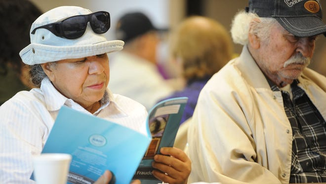 File photo taken in 2013 shows a retiree reading a pamphlet advising senior citizens how to avoid fraud and scams.