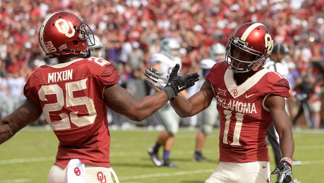 Oklahoma Sooners wide receiver Dede Westbrook (11) and Oklahoma Sooners running back Joe Mixon (25) celebrate a touchdown against the Kansas State Wildcats during the third quarter at Gaylord Family - Oklahoma Memorial Stadium.