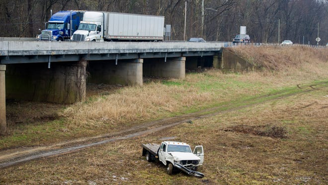 A truck sits in the grass after being knocked over the side of the  U.S. 41 southbound bridge following a multi-vehicle accident, Monday, March 13, 2017. The occupant of the vehicle that went over the bridge was transported to the hospital with non life-threatening injuries.