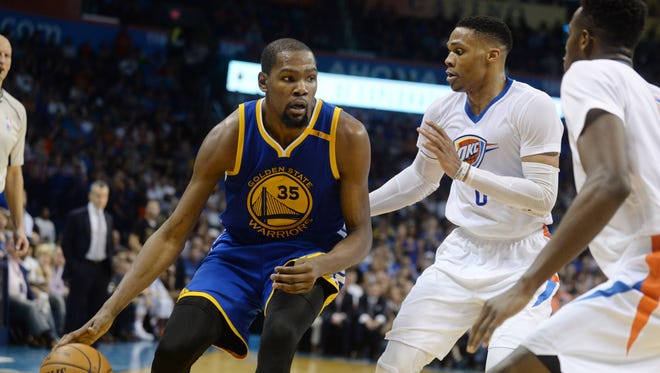 Golden State Warriors forward Kevin Durant fights for position with Oklahoma City Thunder guard Russell Westbrook during the second quarter at Chesapeake Energy Arena.