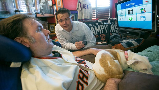 """ALS patient Ron Hunting works with his speech therapist Robert Smith in his """"man cave"""" at his home in Peoria on Tuesday, July 21, 2015."""