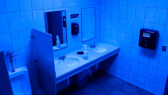 In this June 22, 2018 photo, a public bathroom bathed in blue light is seen at this Turkey Hill convenience store in Wilkes-Barre, Pa. The chain has installed the blue light bulbs in as many as 20 stores in hopes of discouraging drug use by making it harder for people to see their veins.