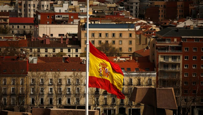 A Spanish flag flies at half staff for the victims of the Germanwings passenger jet, in Madrid. The plane carrying 150 people crashed Tuesday in the French Alps region as it traveled from Barcelona to Duesseldorf in Germany.