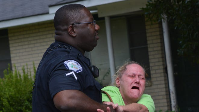 Connie LeBlanc, mother of Christopher LeBlanc, is held by a Pineville Police officer Monday morning at the scene where her son was shot to death on Cummins Street. Christopher LeBlanc allegedly charged an officer with a machete as police arrived to investigate a disturbance call.