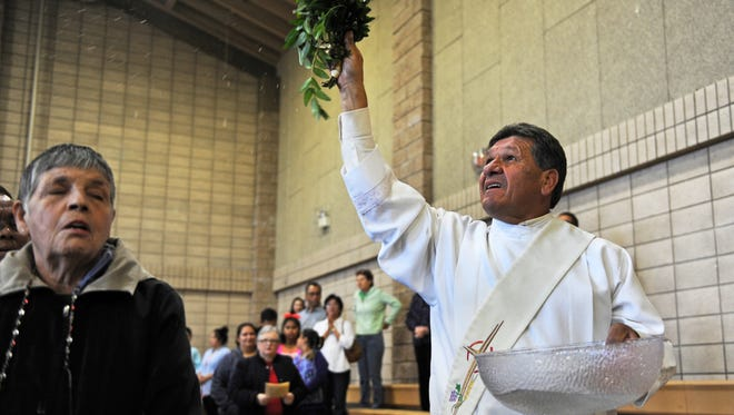 Showering congregants with holy water, Deacon Rick Gutierrez of Sacred Heart Church in Salinas begins the 9:00 AM Mass on Easter Sunday.